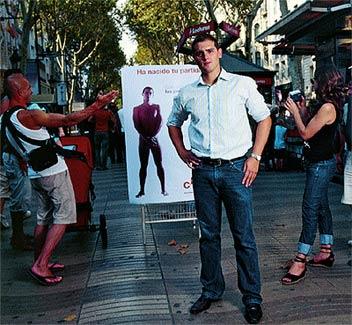 Albert posa vestido junto al cartel electoral en el que aparece desnudo.