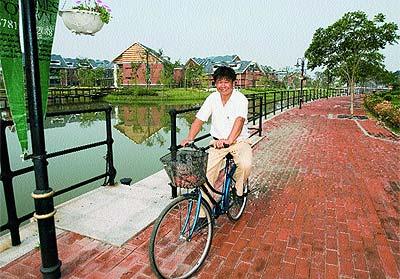 . Un ciudadano chino pedalea tranquilamente por uno de los paseos de Thames Town,