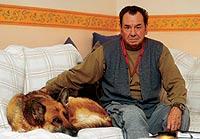Almirón, 70 años, con su perra, en el salón de su casa de Torrent, Valencia. / JOAN MANUEL BALIELLAS
