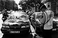 Un policía municipal multa a un coche aparcado en doble fila en Madrid. / DIEGO SINOVA