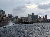 Rompen las olas en el Malecón. Cuando se pone el sol, el muro que protege a la vieja ciudad de La Habana se llena de enamorados, curiosos y turistas. / SARA F. CUCALA
