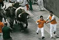 El madrileño Luis Miguel Gómez tira de su hijo David durante el encierro de Sanfermín. / ELOY ALONSO