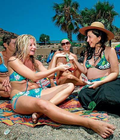 Después de varias horas intentando vender abalorios, la arena le recuerda cada vez más a la del desierto. Eugenia Rico, embarazadísima y con sombrero, no pierde la sonrisa. Sabe que ésta es la mejor arma de trabajo para un vendedor ambulante.
