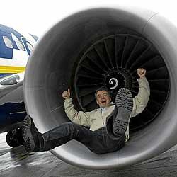 El presidente de Ryanair, Michael O'Leary, en el interior de una de las turbinas de un avión, en una visita al aeropuerto de Santiago de Compostela. / AFP