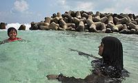 Una madre cubierta con «hijab» (pañuelo) y su hija se bañan en Male, la capital de Maldivas, junto a la gran muralla que protege la isla de la subida del nivel del mar. (Foto: David Jiménez)