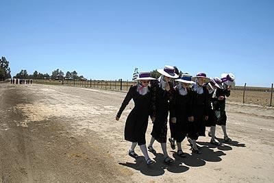 En la calle. Seis jóvenes de Nueva Esperanza pasean con el habitual atuendo de la comunidad: vestido largo y oscuro, medias y sombrero. El pañuelo blanco indica que están solteras. Al casarse, lo cambian por uno negro.