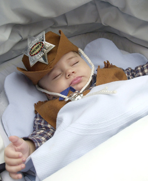 Un bebé disfrazado de 'sheriff' duerme en su cochecito. FOTO: EL MUNDO.