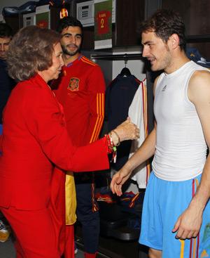 La Reina, con traje rojo y fular amarillo, saluda a Casillas en el vestuario. FOTO: Gtresonline